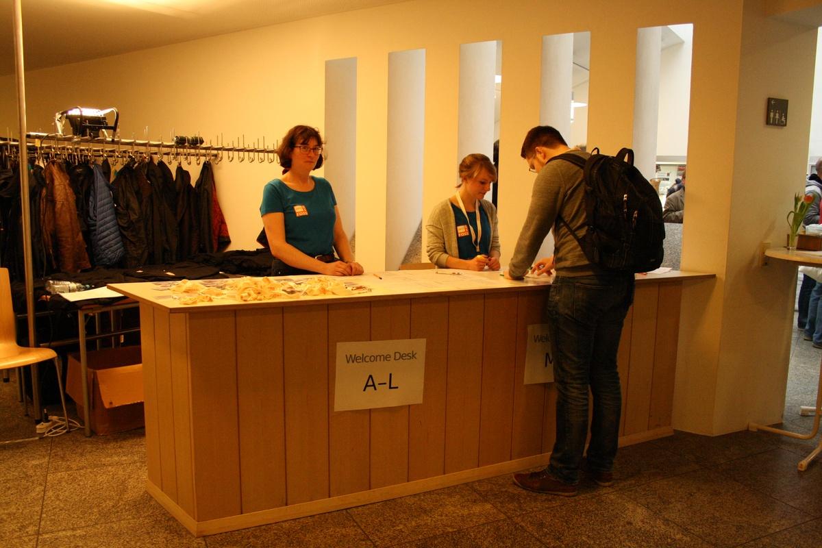 Der Welcome Desk der FOSSGIS mit Schildern A-L und M-Z