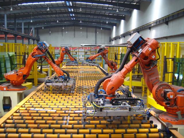 Foto, welches vier Industrieroboter bei der Aufnahme von Glasscheiben zeigt